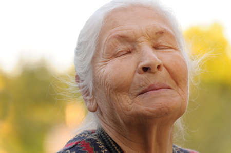 closed eye: The elderly woman with closed eyes. A photo outdoors