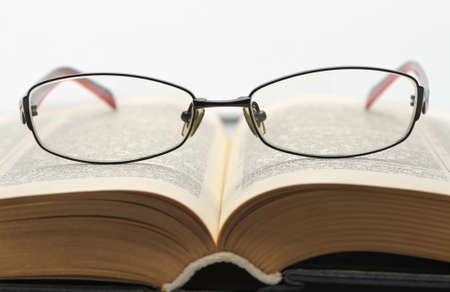 Eyeglasses on the old thick book. Isolated on white background photo