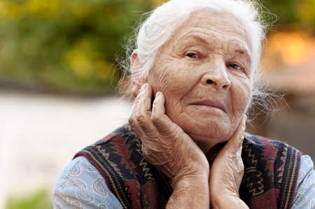 warmly: Portrait of the elderly woman. A photo on outdoors