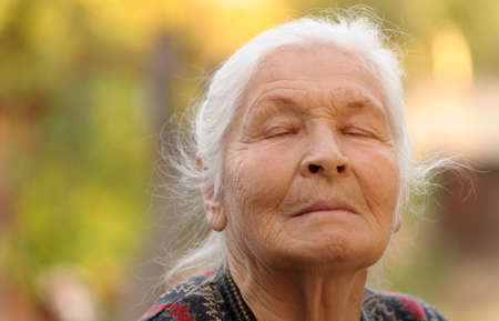 gray eyes: The elderly woman with closed eyes. A photo outdoors