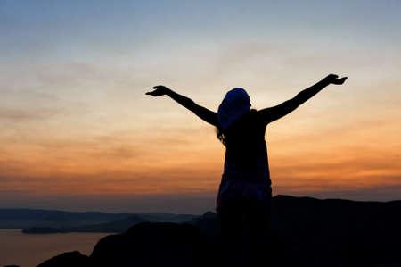 mujer rezando: La mujer en la montaña con los brazos abiertos da la bienvenida a una caída.