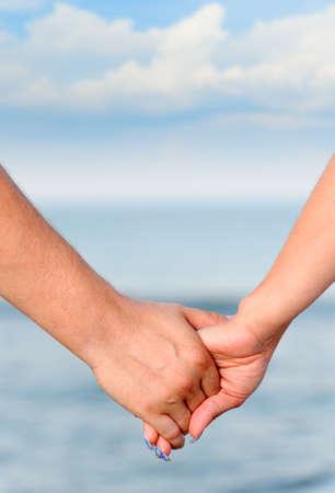 parejas caminando: El hombre y la mujer de la torre del homenaje de manos. Contra el mar y el cielo Foto de archivo