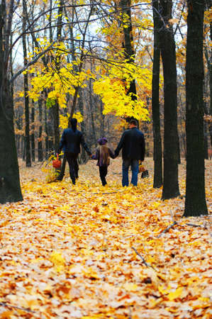 Family in autumn forest. Walk for hands of a happy family from three persons photo