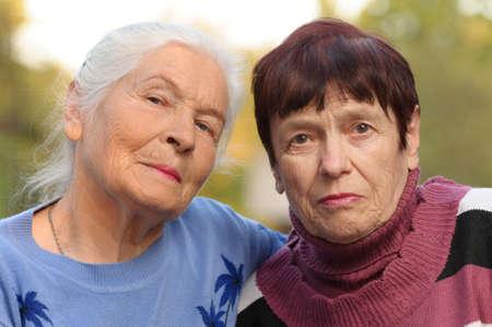 vejez: Dos hermanas de edad avanzada. Una foto en el exterior