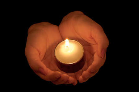 burning love: Burning candle in female hands. A black background Stock Photo