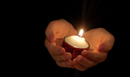 Burning candle in female hands. A black background Stock Photo