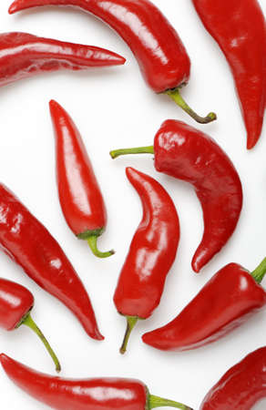 randomly: Red bitter pepper. It is spread randomly out on a white background
