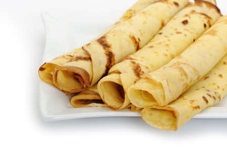 Crepe roll up a tubule on a plate. It is isolated on a white background. Stock Photo