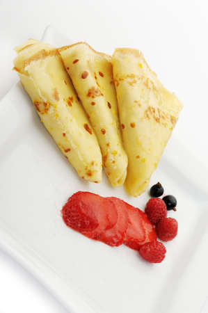 Crepe on a plate with a strawberry, a raspberry and a bilberry. It is isolated on a white background. photo