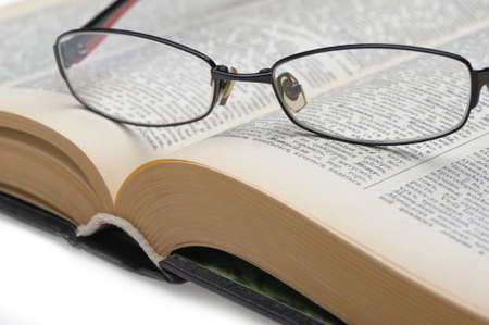 educations: Eyeglasses on the old thick book. A photo close up