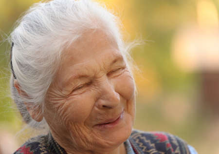 Portrait of the laughing elderly woman. A photo on outdoors Banco de Imagens