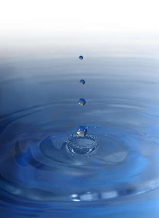 Drop falling in water. High-speed shooting, a blue background Stock Photo - 11205416