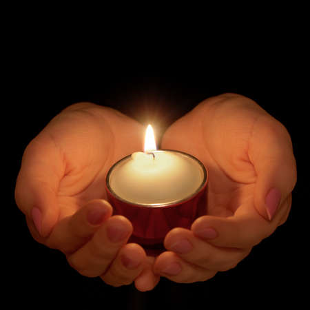 Burning candle in female hands. A black background Imagens