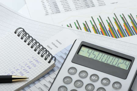 financial item: The calculator and the financial report. A workplace of the businessman