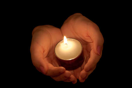 Burning candle in female hands. A black background Stock Photo - 11205587