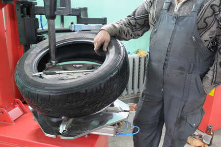 mechanician: The car mechanician changes a tyre cover on an automobile wheel. Stock Photo
