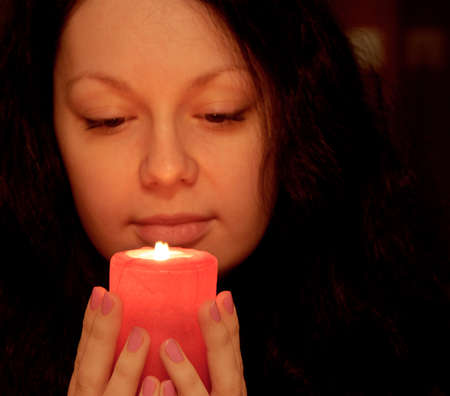 prayer candles: The woman with burning candle. Selective focus on a candle Stock Photo