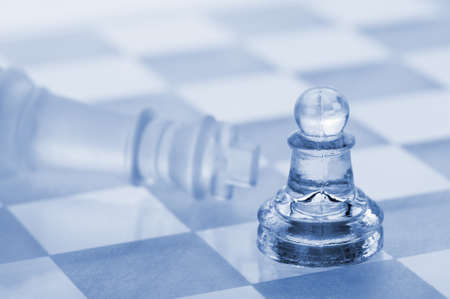 Glass chess. A victory of a pawn over a king. Blue toned. photo