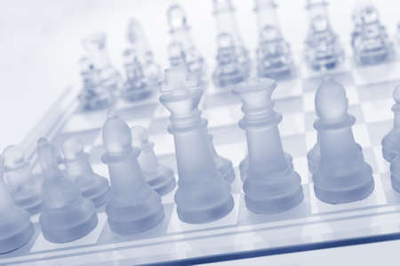chessmen: Glass chess. The first move. Blue toned. Stock Photo