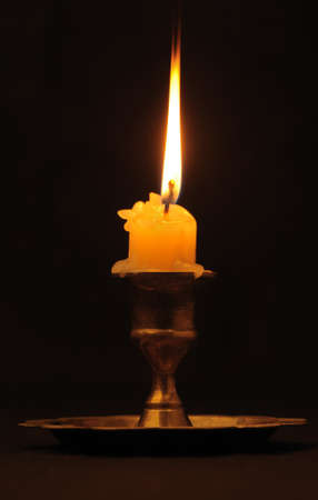 Burning candle. An ancient candlestick, a dark background photo