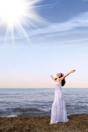 glädje: Kvinnan i en vit sundress på havskusten med öppna händer. Sön ljus