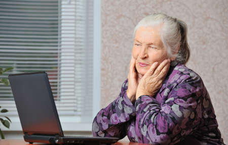 The elderly woman in front of the laptop. A photo in a room photo