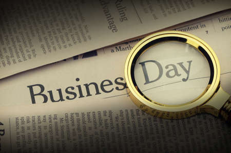 Loupe lies on the newspaper with title Business day. Selective lighting on an inscription.A photo close up. Selective focus photo