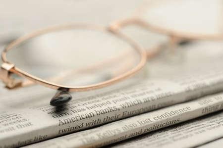 actuality: Occhiali da vista si trovano su una pila di giornali. Una foto da vicino. Messa a fuoco selettiva
