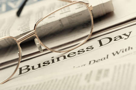 Eyeglasses lie on the newspaper with title Business day. A photo close up. Selective focus photo