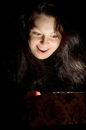 The woman with a gift box. Emotion a surprise. Light from a box. photo