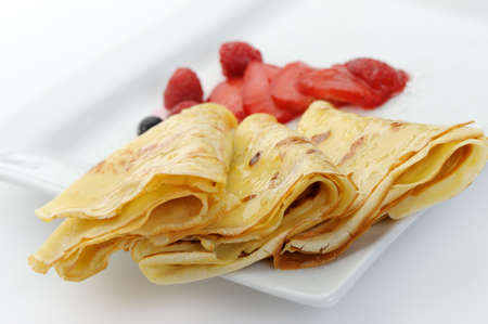Crepe on a plate with a strawberry, a raspberry and a bilberry. It is isolated on a white background.