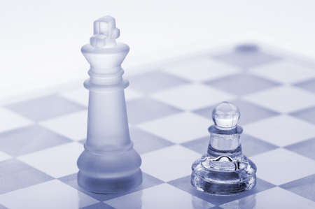 Glass chess. A pawn and a king. Blue toned. It is isolated on a white background. photo