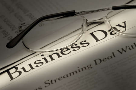 Eyeglasses lie on the newspaper with title Business day. Selective lighting on an inscription. A photo close up. photo