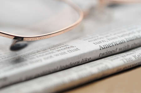 commentary: Eyeglasses lie on a pile of newspapers. A photo close up. Selective focus Stock Photo