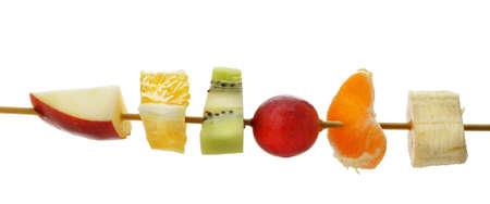 brochetas de frutas: Rebanadas de fruta en un palito de madera. Una foto detallada sobre un fondo blanco