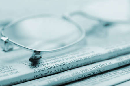 commentary: Eyeglasses lie on a pile of newspapers.Blue toned. A photo close up. Selective focus