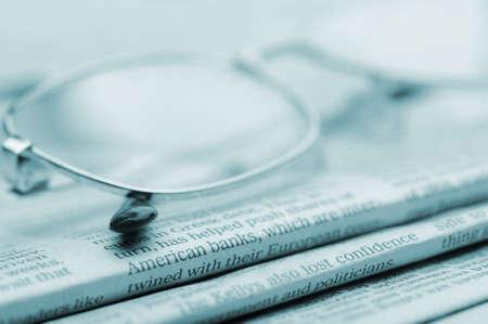 commentary: Los anteojos se encuentran en un mont�n de tonos newspapers.Blue. Una foto de cerca. Enfoque selectivo