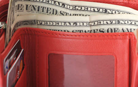 Red leather wallet with dollars and credit cards.Photo closeup photo