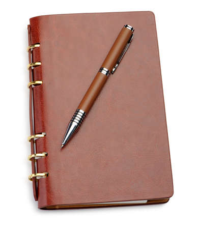 Notebook in a brown leather cover and stylish pen. It is isolated on a white background photo
