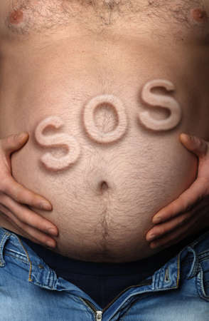 Mans stomach with sticking out inscription SOS. Concept - overweight photo