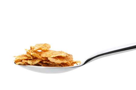 granula: Ð¡ornflakes. A dry breakfast in a spoon. It is isolated on a white background