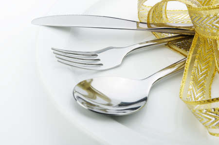 Spoon, fork and a knife tied up celebratory ribbon. Lie on a plate