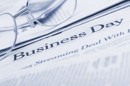 Eyeglasses lie on the newspaper with title Business day.Blue toned. A photo close up. Selective focus Stock Photo