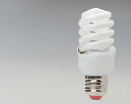 Energy saving compact fluorescent lightbulb on a grey gradient photo