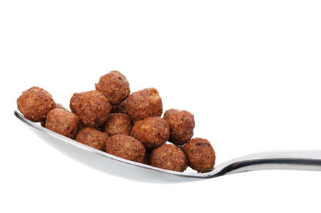 granula: Chocolate cornflakes. A dry breakfast in a spoon. It is isolated on a white background