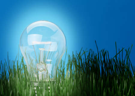 Shone electric lamp in a grass. A blue background photo