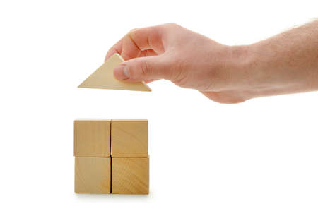 wood blocks: The hand establishes a toy roof on wooden cubes. Isolated on white