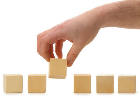 yellow block: The hand establishes a wooden cube in row. It is isolated on a white background Stock Photo