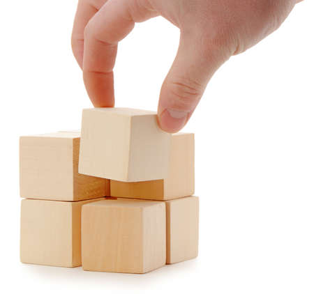 The hand establishes a wooden cube. It is isolated on a white background photo