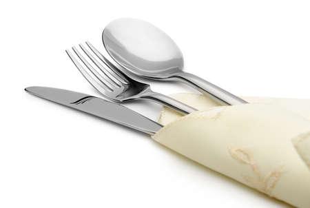servilleta de papel: Cuchara, tenedor y cuchillo en una mentira servilleta. Es aislados sobre un fondo blanco